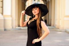 Attraktive junge Dame in einem schwarzen Hut Stockfoto