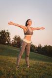 Attraktive junge Eignungsfrau, die im Park übt Sportbetrug Stockbild