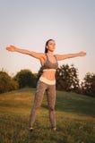 Attraktive junge Eignungsfrau, die im Park übt Sportbetrug Stockfotos