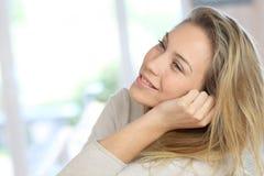 Attraktive junge entspannende Frau zu Hause Stockbild