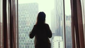 Attraktive junge Frau öffnet Vorhangblicke am Fenster in der Wohnung und genießt von der Stadtansicht von der Höhe 3840x2160 stock video