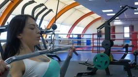 Attraktive junge Frau arbeitet auf einer Eignungsstation in der Turnhalle aus und pumpt Eisen Abgehendes Frauentraining mit Abris stockbild