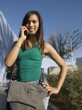 Attraktive junge Frau auf Zelle lizenzfreie stockfotografie