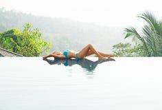 Attraktive, junge Frau in cyan-blauer Badeanzug Lügenpoolside Lizenzfreie Stockfotografie