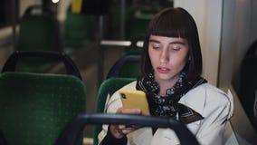 Attraktive junge Frau in der Tram unter Verwendung des Smartphone plaudernd mit Freunden Langsame Bewegung Internet, Technologie, stock footage