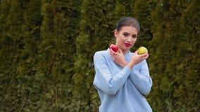 Attraktive junge Frau des Porträts in den Matrosegriffen in ihren Händen grün und in den roten Äpfeln stock video footage