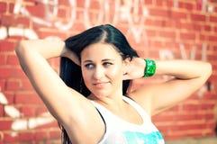 Attraktive junge Frau, die über roter Wand aufwirft stockbilder