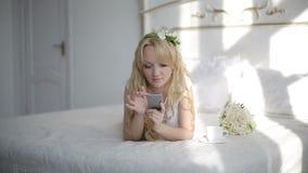 Attraktive junge Frau, die APP auf Smartphone im Schlafzimmer verwendet steadicam Schuss stock video