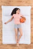 Attraktive junge Frau, die auf Bett liegt Lizenzfreie Stockbilder
