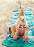 Attraktive junge Frau, die auf dem Strand mit der Weinlese bunt liegt Lizenzfreies Stockfoto