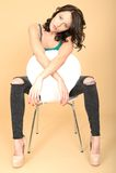 Attraktive junge Frau, die auf einem Stuhl in den Schuhen des hohen Absatzes sitzt und Stockbilder