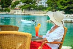 Attraktive junge Frau, die auf einem tropischen Strand sich entspannt Stockbilder