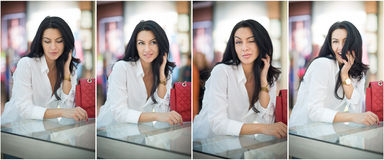 Attraktive junge Frau, die auf einer Tabelle im Einkaufszentrum sitzt Schöne moderne junge Dame im weißen Hemd im Mall Stockbild