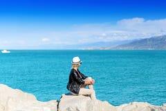 Attraktive junge Frau, die auf Felsen sitzt Lizenzfreie Stockbilder