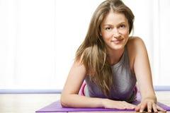 Attraktive junge Frau, die auf ihrer Yoga-Matte liegt Stockbild