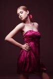 Attraktive junge Frau, die auf rosafarbenem Kleid trägt Stockbilder