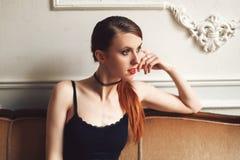 Attraktive junge Frau, die auf Sofa im sexy Spitzenoberteil sitzt und aufwirft lizenzfreies stockbild