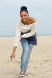 Attraktive junge Frau, die auf Strand lächelt und geht Stockfotografie