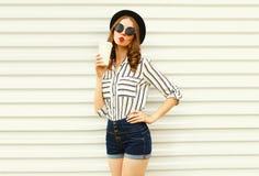 Attraktive junge Frau, die den süßen Luftkuß hält Kaffeetasse im schwarzen runden Hut, kurze Hosen, weißes gestreiftes Hemd auf W lizenzfreie stockfotos