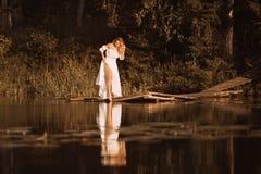 Attraktive junge Frau, die den See zeigt ihre sexy Beine bereitsteht stockbild