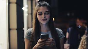 Attraktive junge Frau, die den Smartphone geht auf die Straße der Nachtstadt glücklich reagierend zur Mitteilung verwendet modern stock video