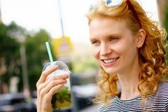 Attraktive junge Frau, die in der Hand mojito hält stockfotos