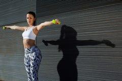 attraktive junge Frau, die Dummköpfe verwendet, um ihre Arme bei auf Kopienraumhintergrund draußen ausbilden auszuarbeiten Lizenzfreie Stockbilder