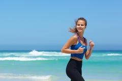 Attraktive junge Frau, die durch das Meer läuft Lizenzfreie Stockfotografie