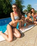 Attraktive junge Frau, die durch das Pool im Hintergrund seiner Freunde ein Sonnenbad nimmt Stockfotos