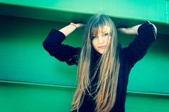 Attraktive junge Frau, die durch die Wand aufwirft stockfoto