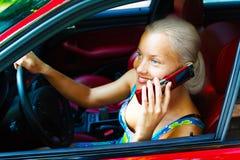 Attraktive junge Frau, die durch Mobiltelefon benennt stockfoto