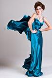 Attraktive junge Frau, die ein blaues Satin-Kleid trägt Stockfotos