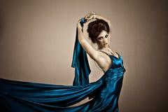 Attraktive junge Frau, die ein blaues Satin-Kleid trägt Stockfoto