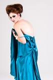 Attraktive junge Frau, die ein blaues Satin-Kleid trägt Stockbilder