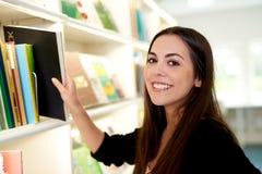 Attraktive junge Frau, die ein Buch ein Regal entfernt lizenzfreie stockfotos