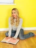 Attraktive junge Frau, die ein Buch lesend studiert Lizenzfreie Stockfotografie