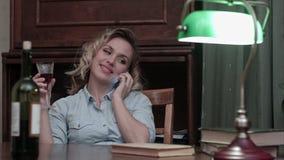 Attraktive junge Frau, die ein Glas Wein sitzend an ihrem Schreibtisch bei der Unterhaltung am Telefon nach einem langen Arbeitst stock video footage