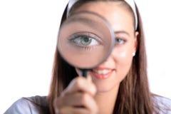 Attraktive junge Frau, die ein Vergrößerungsglas verwendet stockfotografie
