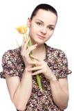 Attraktive junge Frau, die eine gelbe Tulpe hält lizenzfreie stockbilder
