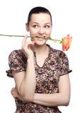Attraktive junge Frau, die eine gelbe Tulpe hält stockfotos