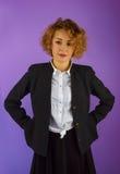 Attraktive junge Frau, die in einem schwarzen Anzug steht lizenzfreie stockfotos