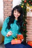 Attraktive junge Frau, die in einem Weihnachtsinnenraum, Griffe bezüglich sitzt stockbild