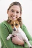 Attraktive junge Frau, die einen Hund und ein Lächeln anhält Stockbild