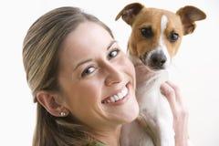 Attraktive junge Frau, die einen Hund und ein Lächeln anhält Lizenzfreies Stockbild
