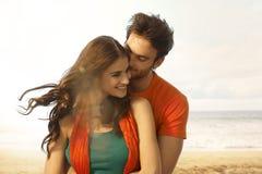 Attraktive junge Frau, die einen Kuss am Strand erhält Lizenzfreies Stockbild