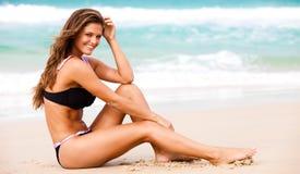 Attraktive junge Frau, die einen schwarzen Badeanzug trägt Stockfotos