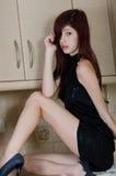 Attraktive junge Frau, die in einer Kücheneinstellung aufwirft lizenzfreies stockfoto