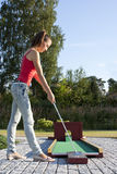 Attraktive junge Frau, die Golfball auf Grün setzt Stockfotos