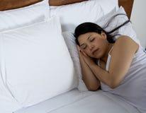 Attraktive junge Frau, die gut im Bett schläft Stockfoto