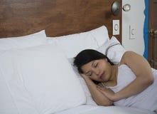 Attraktive junge Frau, die gut im Bett schläft Lizenzfreie Stockfotos